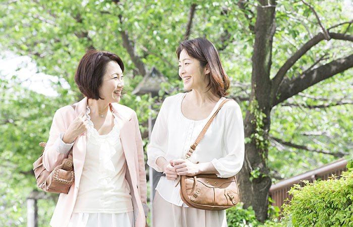 木の下を歩きながら会話をする2人の女性